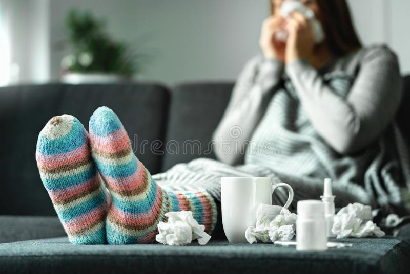 Sick woman with flu, cold, fever and cough sitting on couch at home. Ill person blowing nose and sneezing with tissue. Sick woman with flu, cold, fever and royalty free stock images