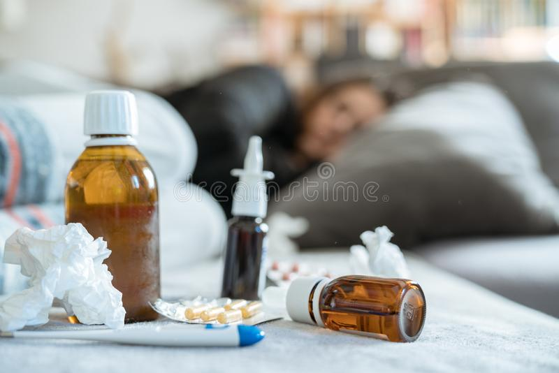 Sick woman with flu, cold, fever or virus sitting on sofa at home. Sick woman resting on couch holding hot cup of tea. Ill person with flu, cold, fever or virus stock image