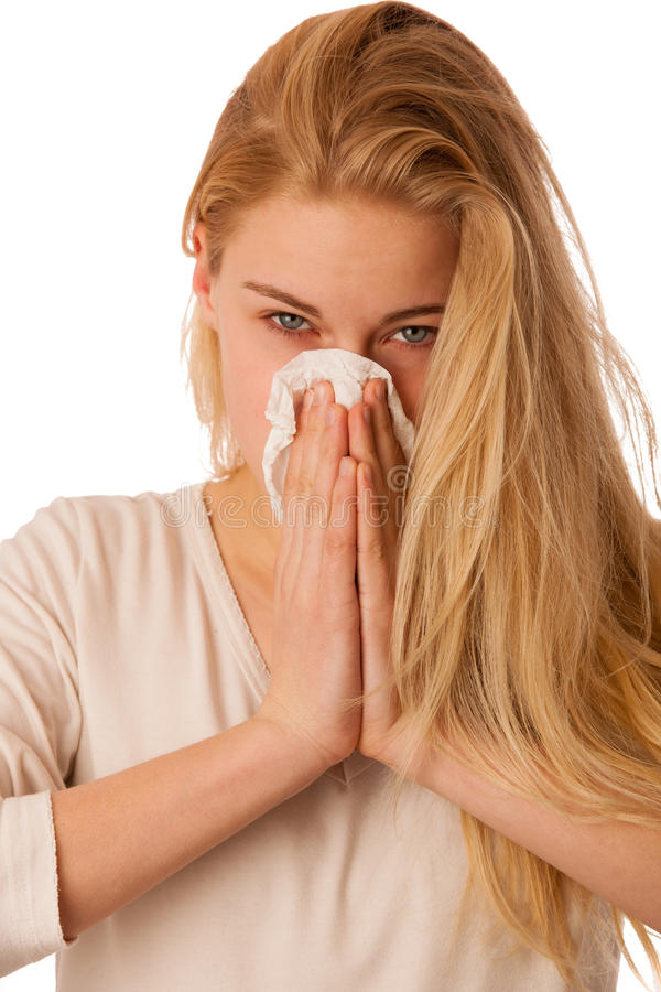 Sick woman with flu and fever blowing nose in tissue isolated over white background. royalty free stock image