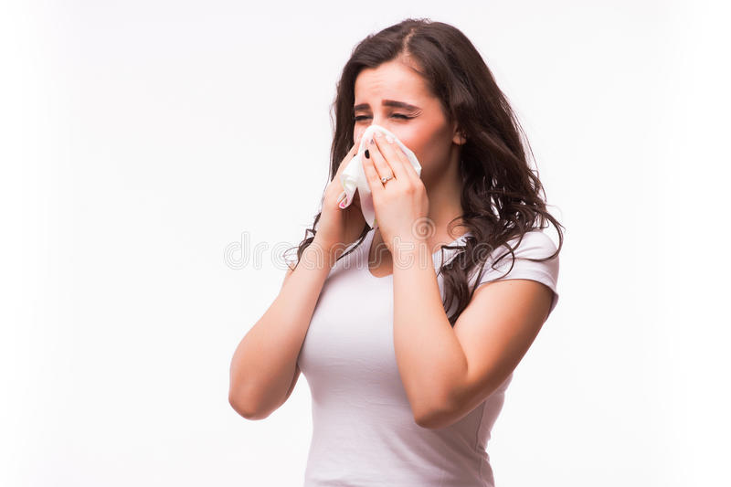 Sick woman with flu and fever blowing nose in tissue stock image