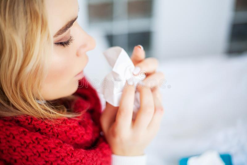 Sick woman with flu. Woman Suffering From Cold Lying In Bed With. Tissue royalty free stock photography