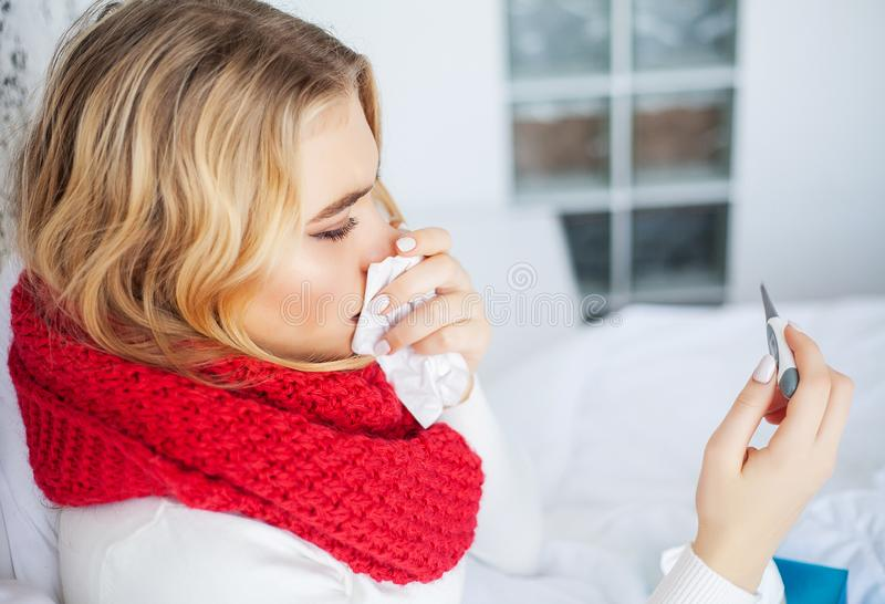 Sick woman with flu. Woman Suffering From Cold Lying In Bed With. Tissue stock image