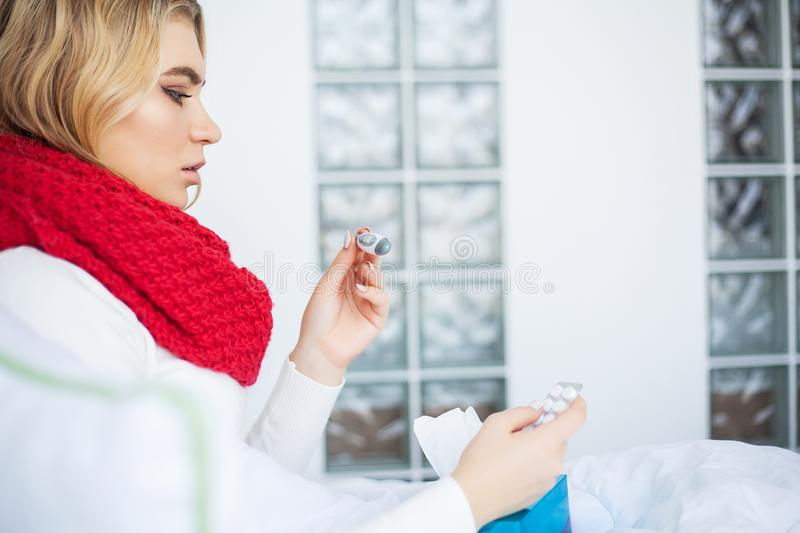Sick woman with flu. Woman Suffering From Cold Lying In Bed With. Tissue royalty free stock photo