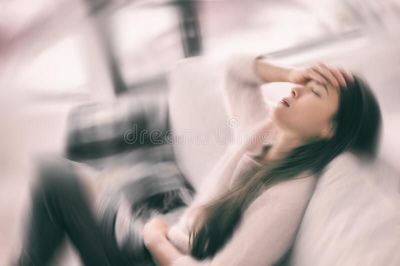 Sick woman with headache feeling faint vertigo holding head in pain with fever and migraine. Blurry motion blur. Background stock photography
