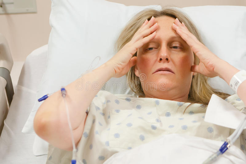 Sick Woman in Hospital. Sick woman in a hospital bed feeling pain or stress royalty free stock image