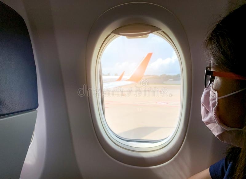Sick woman passenger wear face mask and eyeglasses sit on passenger economy seat near cabin window inside airplane. Passenger royalty free stock images