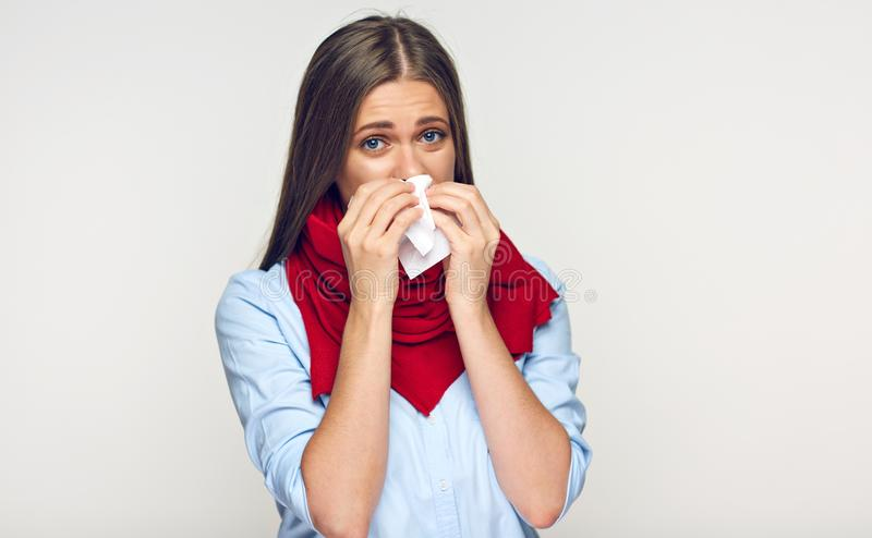 Sick woman with red scarf using tissue. Isolated portrait stock photography