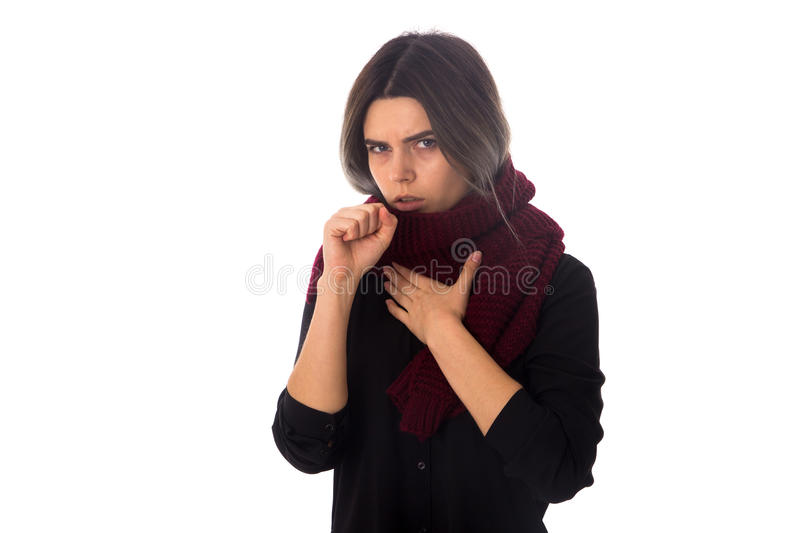 Sick woman with scarf coughing. Young sick woman with dark hair in black blouse with long scarf cuoghing on white background in studio stock images