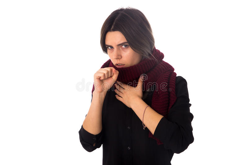 Sick woman with scarf coughing. Young sick woman with dark hair in black blouse with long vinous scarf cuoghing on white background in studio royalty free stock images