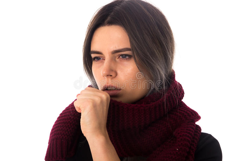 Sick woman with scarf coughing. Young sick woman with dark hair in black shirt with long vinous scarf cuoghing on white background in studio royalty free stock image