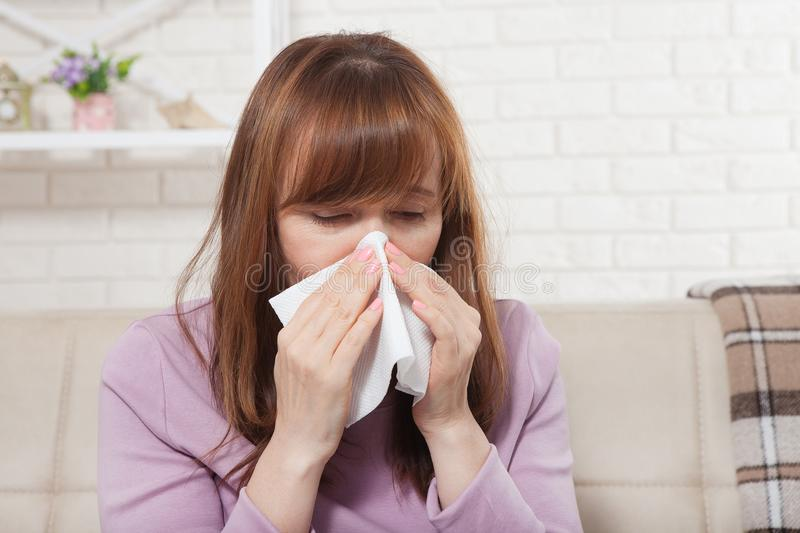 Sick woman sitting at home with high fever. Cold, flu, fever and migraine, sneeze. Copy space. Runny nose stock images