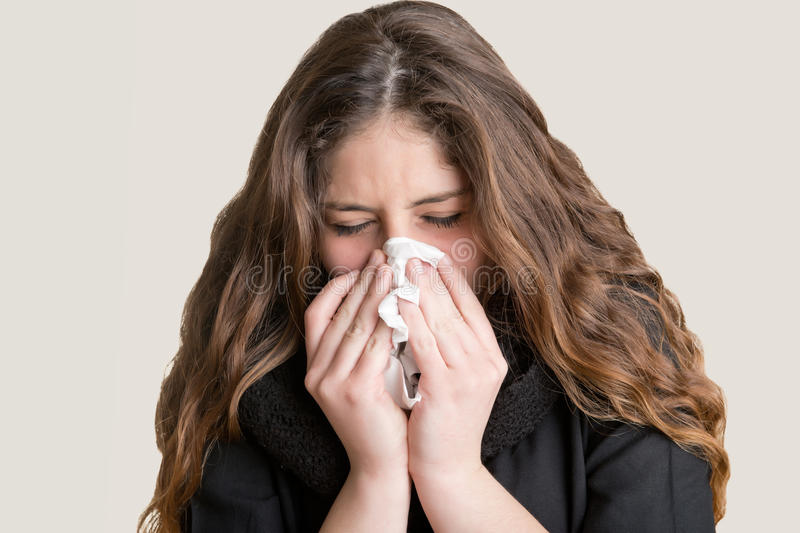 Sick Woman Sneezing. Pale sick woman with a flu, sneezing, in a clean background stock images
