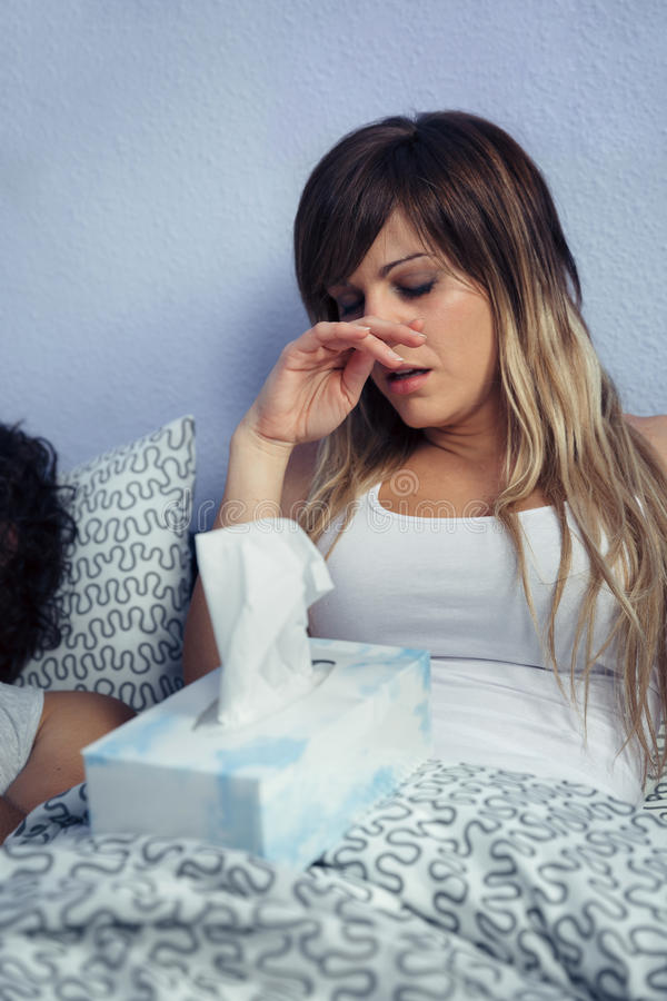 Sick woman with tissues box sitting on bed royalty free stock photos