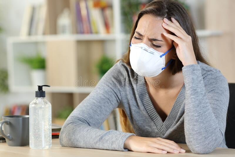 Sick woman suffering covid-19 symptoms at home. Sick woman wearing protective mask with headache suffering covid-19 symptoms at home royalty free stock photos
