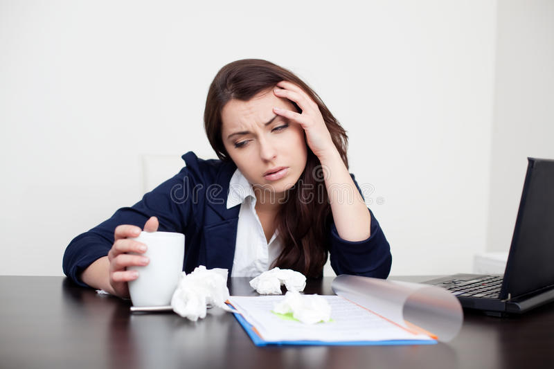 Sick woman at work drinking coffee stock photos