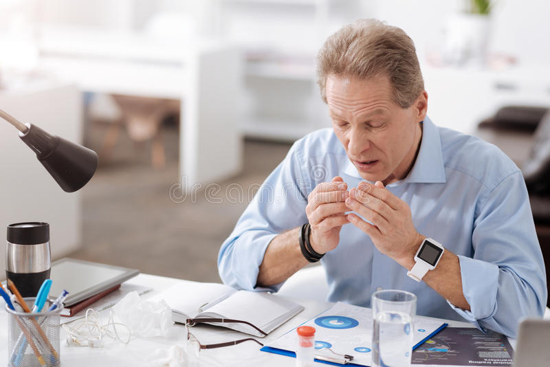 Sick worker while going to sneeze. Bless you. Frustrated man wearing blue shirt, wrinkling his forehead while keeping hands opposite his mouth royalty free stock images