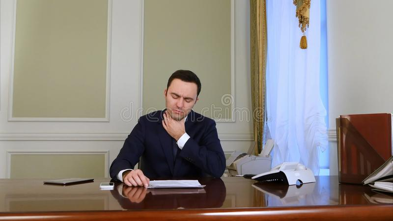 Sick young businessman saffers from cough royalty free stock images
