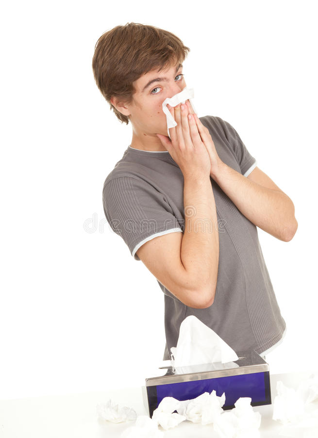 Sick young man with flu blowing her nose