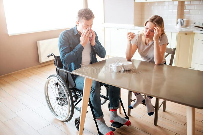 Sick young man with inclusiveness sneezing with healthy woman at table. Sick people in kitchen. Headache and pain royalty free stock images