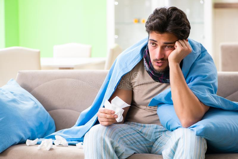 The sick young man suffering from flu at home. Sick young man suffering from flu at home royalty free stock photography