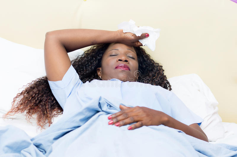 Sick young woman. Sick African woman lying in bed holding white handkerchief in hand stock photography