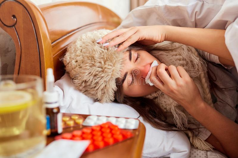 Sick young woman on the bed in the room stock images