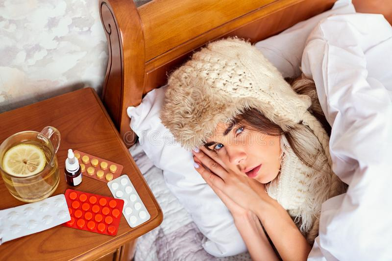 Sick young woman on the bed in the room royalty free stock photography