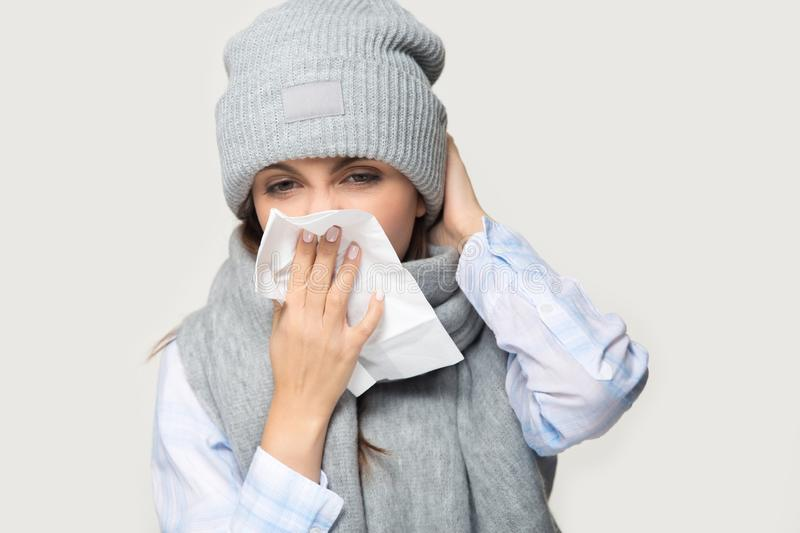 Sick young woman blow nose suffering from flu royalty free stock image