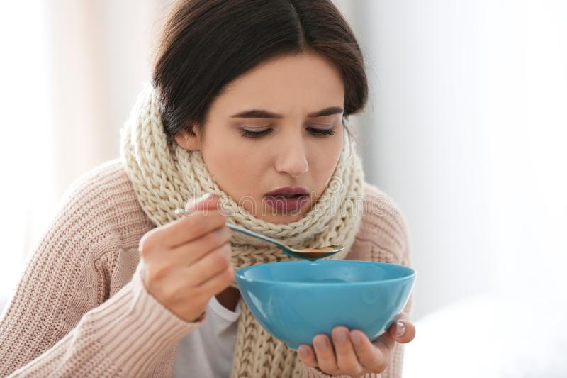 Sick woman eating soup to cure flu. Sick young woman eating soup to cure flu royalty free stock photo