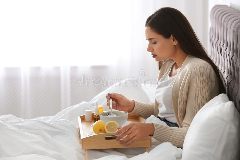 Sick young woman eating soup to cure flu in bed royalty free stock photography