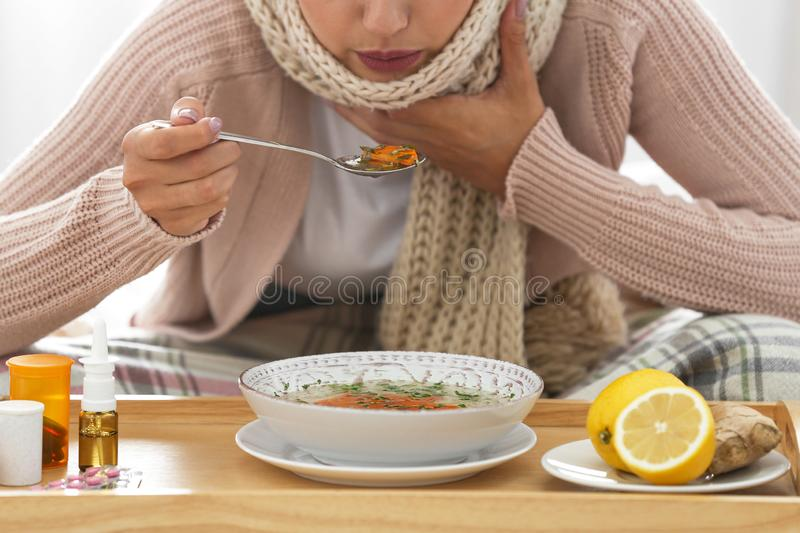 Sick young woman eating soup to cure flu, closeup royalty free stock images