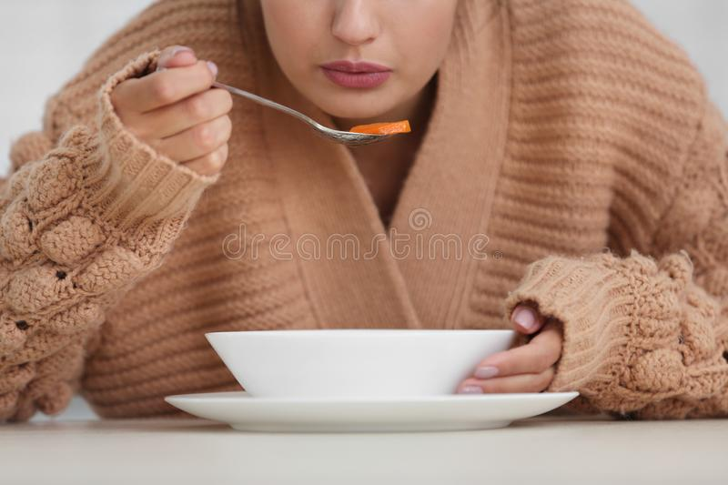 Sick young woman eating soup to cure flu. Closeup royalty free stock image