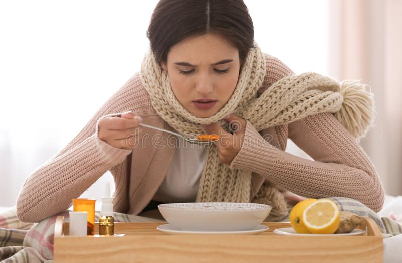 Sick young woman eating soup to cure flu. At home stock photo
