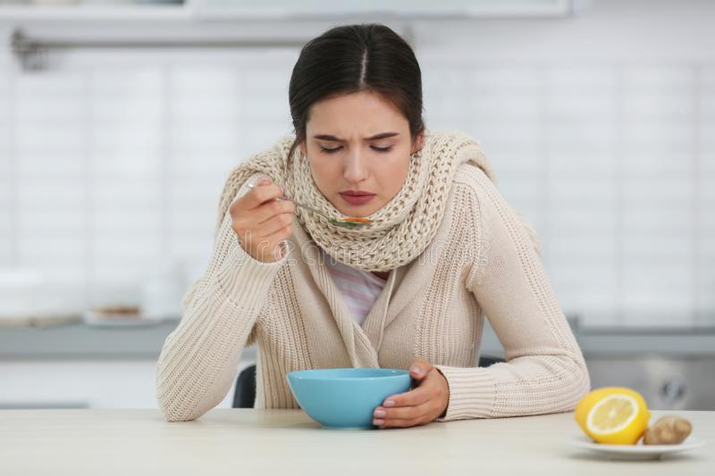Sick young woman eating soup to cure flu at table stock image