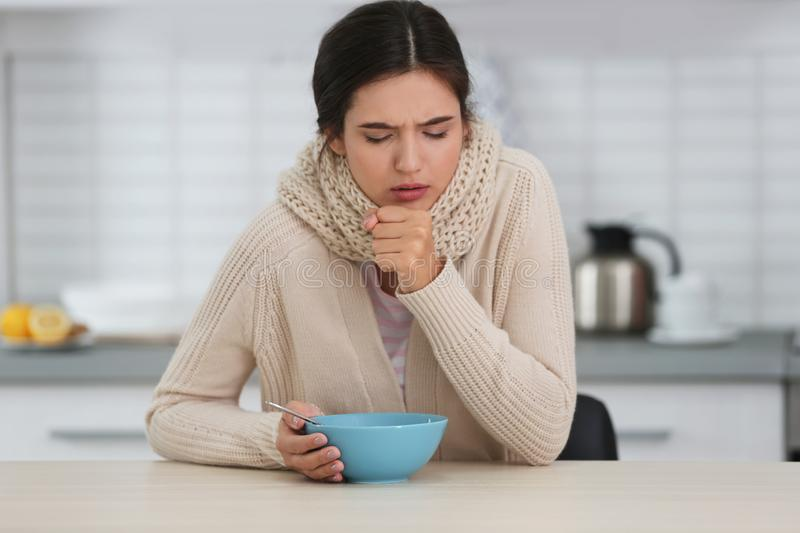Sick young woman eating soup to cure flu at table royalty free stock photo