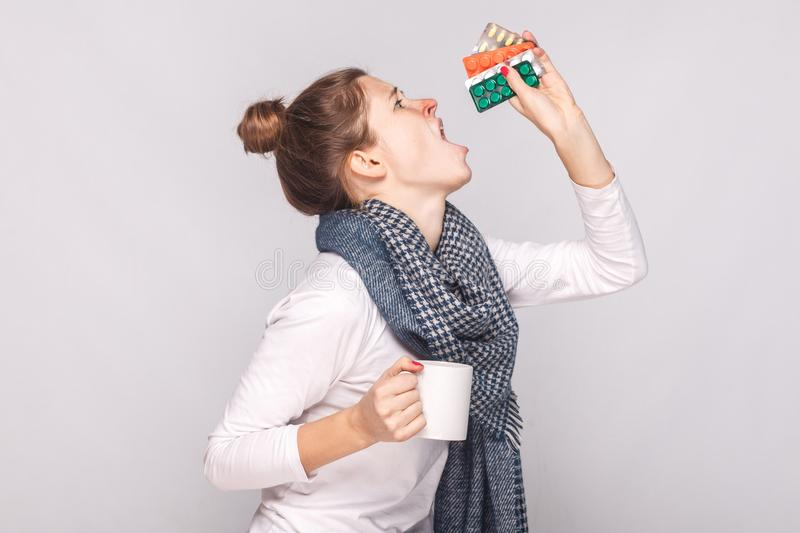 Sick young woman holding cup with tea, many pills, antibiotics. royalty free stock photos