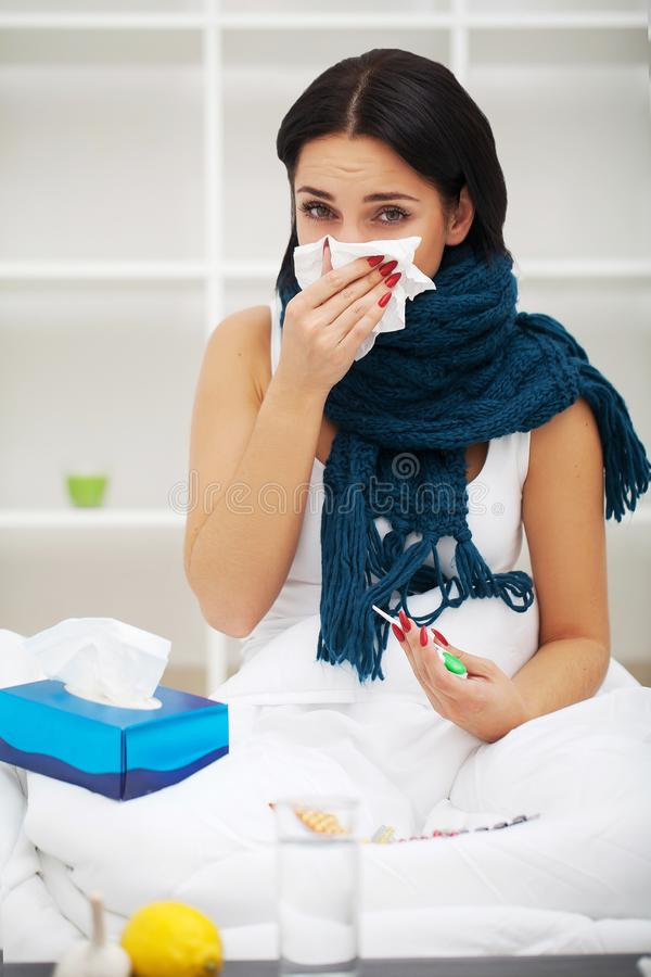 Sick young woman at home on the sofa, she is covering with a blanket, taking temperature and blowing her nose with a tissue stock photo