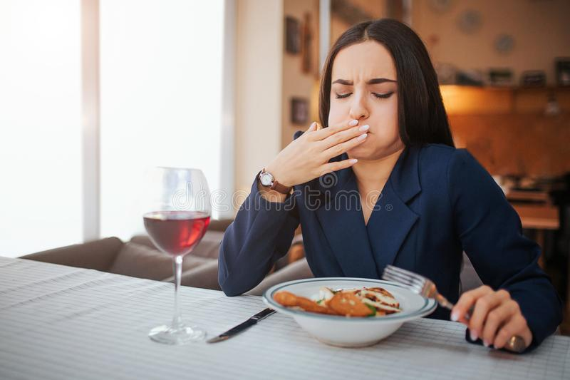Sick young woman start to vomit. She cover mouth with hand and keep eyes closed. Model feels bad. She has glass of red royalty free stock image