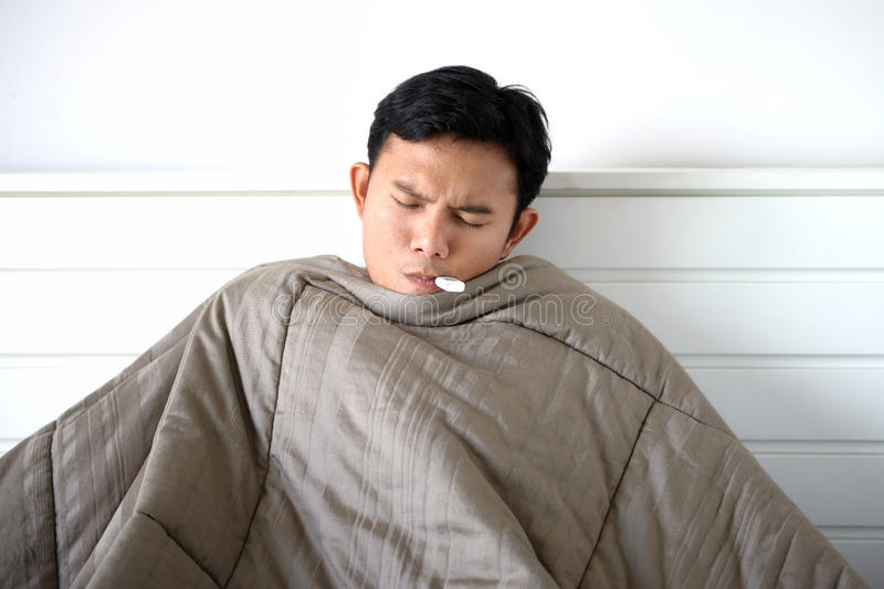 Sickness. Thai young man resting in bed while sickness stock images