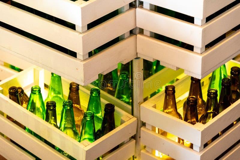 Sicksacken formade hyllor som gjordes från vita målade träspjällådor med gröna och bruna glasflaskor inom Retro stilölflaskarader royaltyfri bild