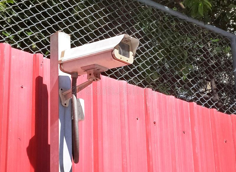 Sicurezza della macchina fotografica del CCTV sulla parete rossa nel parcheggio dell'automobile immagine stock
