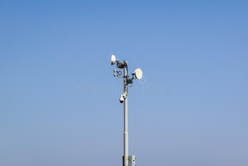 Sicurezza e sistema del satellite con una videosorveglianza, un'antenna ed i piatti di comunicazioni su un palo contro un soleggi immagini stock libere da diritti