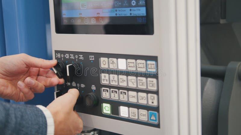 Sicurezza energetica - pannello dell'amministrazione di sistema Il lavoratore dell'uomo manipola per telecomando industriale immagini stock