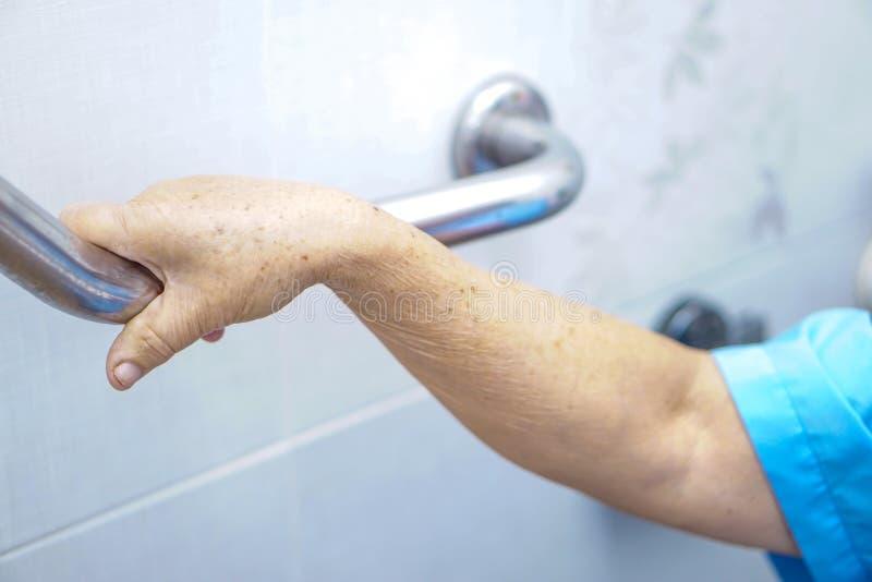 Sicurezza paziente asiatica della maniglia della toilette di uso della donna senior o anziana della signora anziana nell'ospedale immagine stock