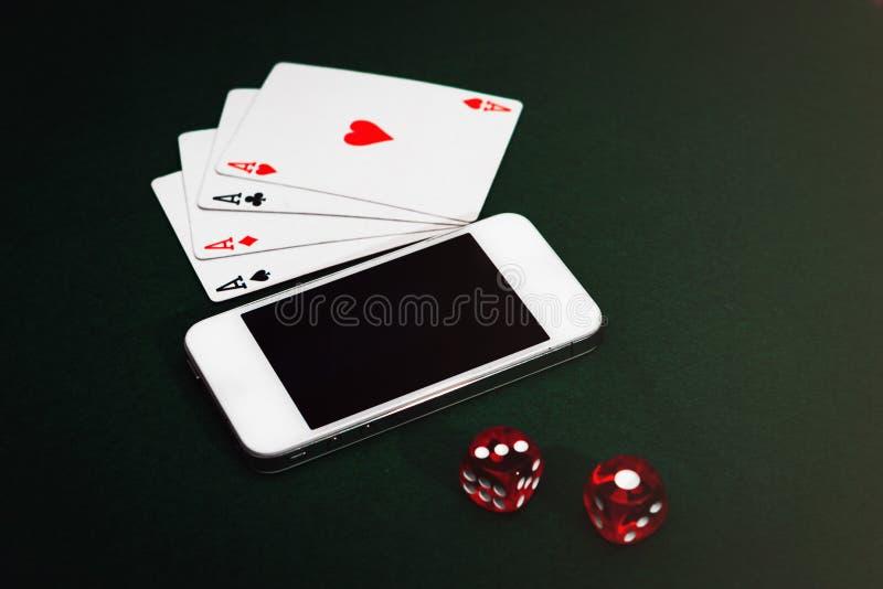 Sid tärnar sikten av en grön pokertabell med en smartphone, kort och Spela appböjelse arkivbild
