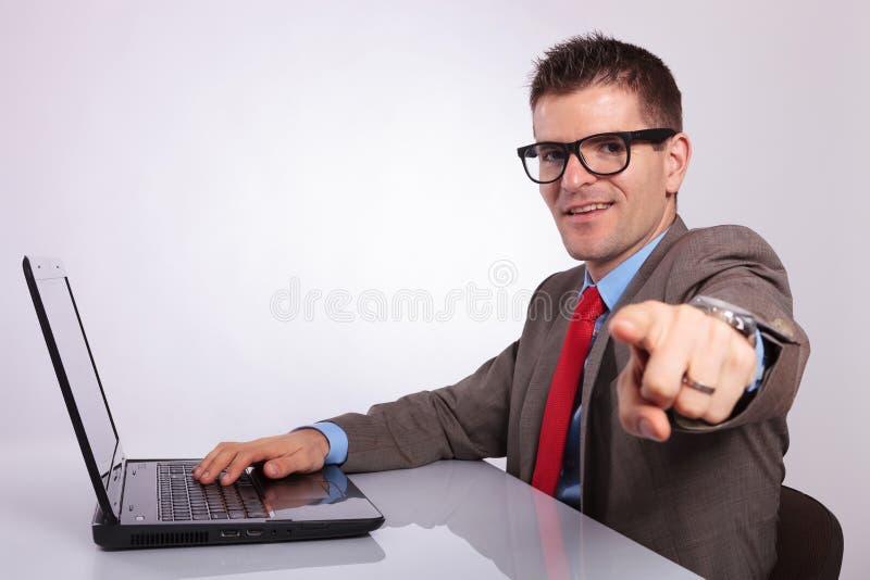 Sida av den unga affärsmannen på bärbara datorn som pekar på dig royaltyfri foto