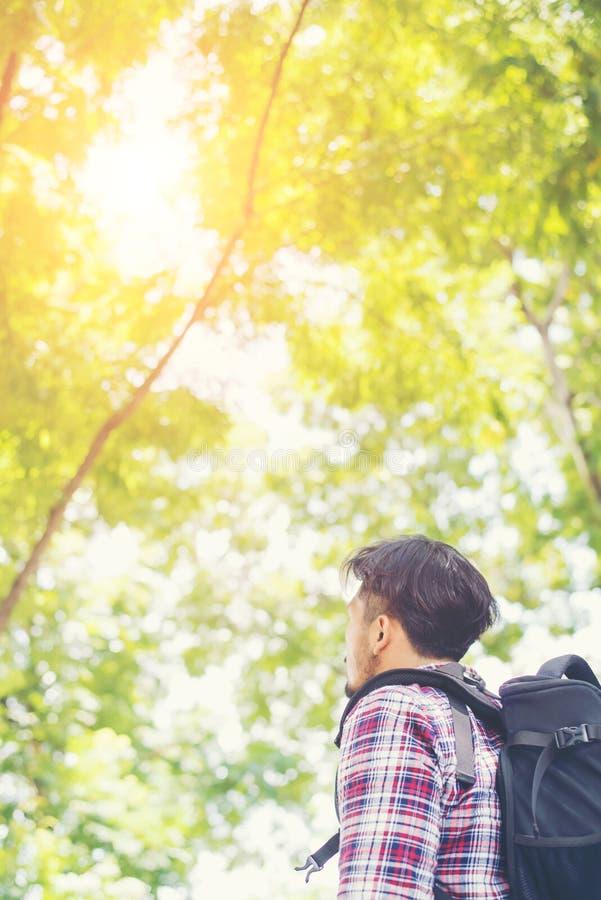 Sida av den unga handelsresandemannen för hipster som ser till naturen, enjoyi arkivbild