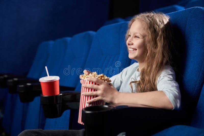 Sida av en lycklig tjej som skrattar åt en rolig komedi på bio royaltyfria bilder