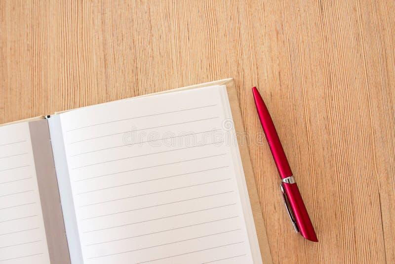 Sida för anteckningsbok för mellanrum för kontorsskrivbord och röd penna på wood kontorstabl arkivfoto