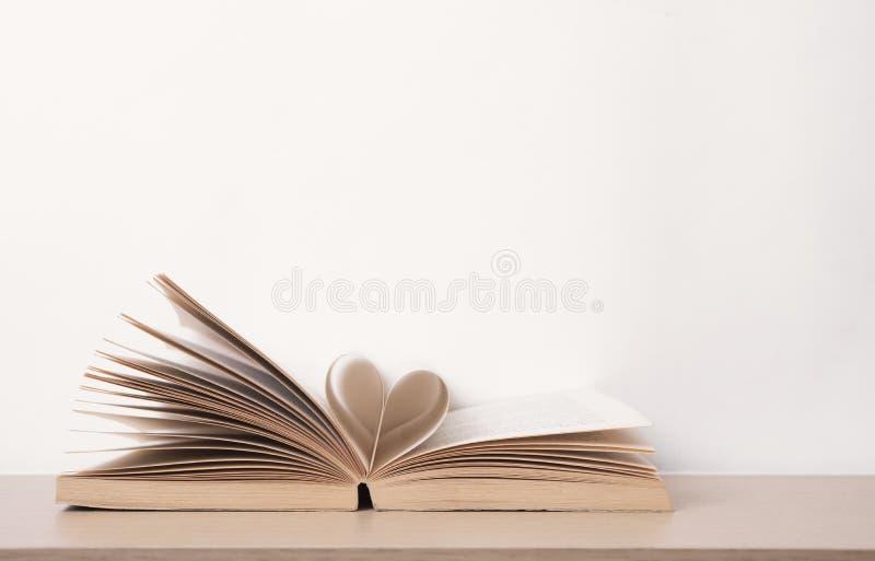 Sidan av boken buktade in i hjärtaform på den wood tabellen valentin royaltyfria bilder